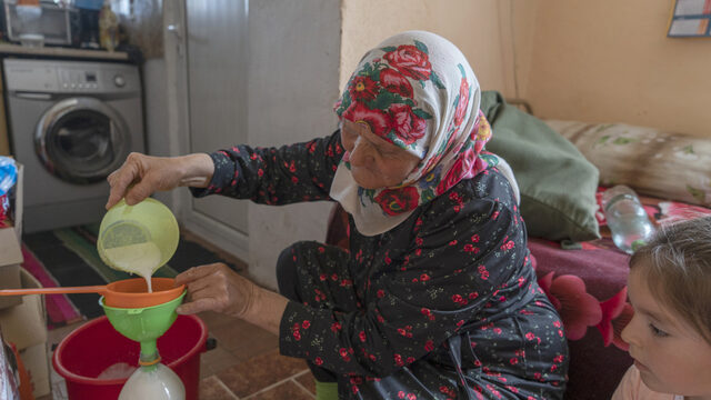 Sabie pours milk through a sieve to remove any impurities as she bottles it in used cola bottles and then delivers to customers in Velingrad. Her granddaughter, also named Sabie, watches. Most younger community members aren't following their parents' example and the tradition will likely die out.