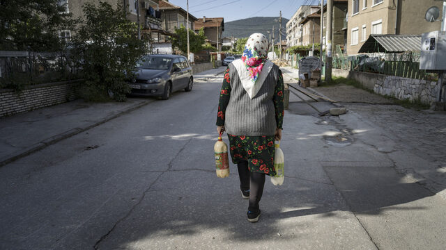 Sabie Djikova carrying bottles of milk on her delivery route in Velingrad. Several other women do the same thing. Each has her own area.