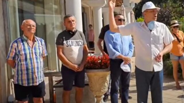 Dogan (on the left) with the leader of his party (on the right) in front of his summer residence during last year's protests
